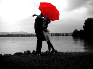 couple kissing under red umbrella