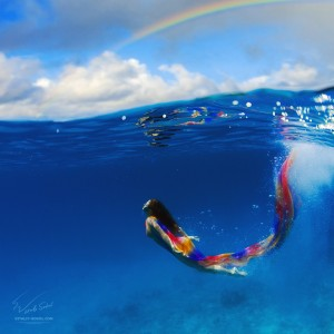 Underwater fashion. Beautiful model swimming underwater wearing colorful clothes with spray of air bubbles